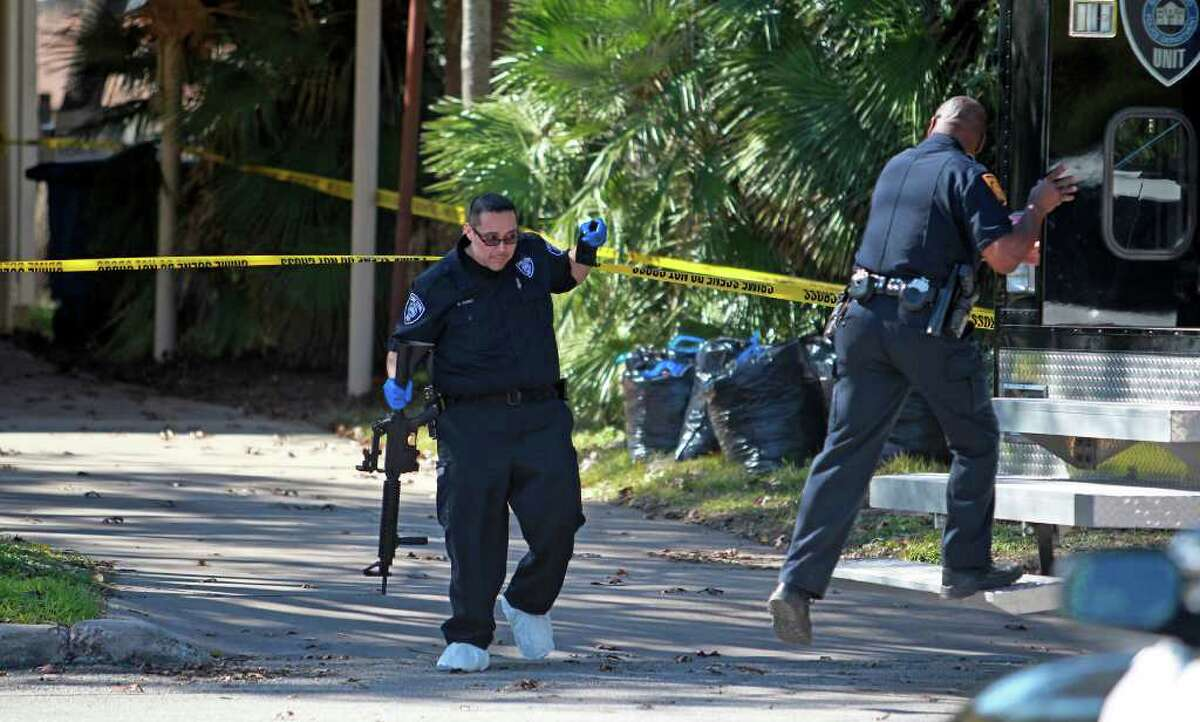 An officer carries a rifle from the scene of a shootout after a home invasion on the Northeast Side Wednesday, Jan. 11, 2012.