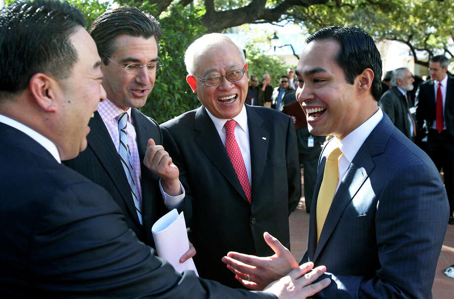 Mayor Julián Castro talks with OCI representative Woo Jeong Lee (from left), Kirk Milling and Greg Baik as CPS Energy announces OCI Solar Power as the choice to bring a 400-megawatt solar power plant to San Antonio at LaVillita Assembly Hall on Jan. 11, 2012. Photo: Tom Reel, San Antonio Express-News