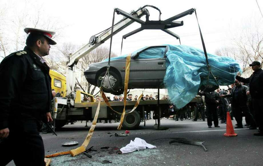 "People gather around a car — its driver and passenger, a nuclear scientist, killed — as it is removed in Tehran. Iran blames ""the Zionists,"" but the U.S. and Israel each denies responsibility. Photo: MEGHDAD MADADI, AP, FARS NEWS AGENCY"