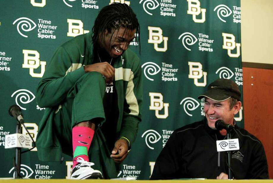 Heisman Trophy winner Robert Griffin III (left) shows off his Barney character socks to Baylor coach Art Briles. The QB wore them to his farewell news conference because he loves everybody. Photo: AP