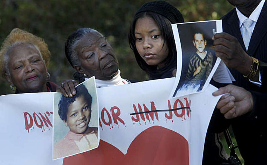 Emani Washington (right), the Rev. Olivia Williams (center) and Geraldine Sword (left) held pictures of children who died at Jonestown. Jonestown survivors and supporters gathered at Evergreen Cemetery Monday February 28, 2011 in Oakland, Calif., to protest the cemetery's decision to put together a memorial including the name of cult leader Jim Jones. Photo: Brant Ward, The Chronicle