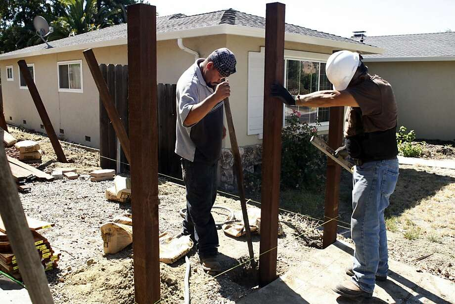 David Cortez, left, and Andres Castaneda build a fence around one of the homes Waypoint is renovating on Monday, August 15, 2011. Waypoint Homes buys foreclosed homes, fixes them up and rents them out with an option to buy. It owns about 700 homes in Contra Costa and Solano counties. Photo: Maddie McGarvey, The Chronicle