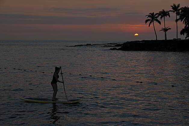 A stand-up paddle surfer takes advantage of the last rays of light to head to shore at Kailua-Kona's Kamakahonu Beach. Photo: Jeanne Cooper, Special To The Chronicle