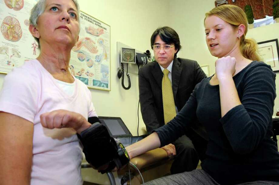 Occupational therapist Amy Boos assists an aneurysm patient, Kathy Riordan, with the mPower 1000 in neurologist Dr. Frederick Nahm's Greenwich office as Nahm looks on. Manufactured by the neurorobotics company Myomo, the robotic device harnesses patients' own limited muscle movement to help them use their arms. Photo: Helen Neafsey / Greenwich Time
