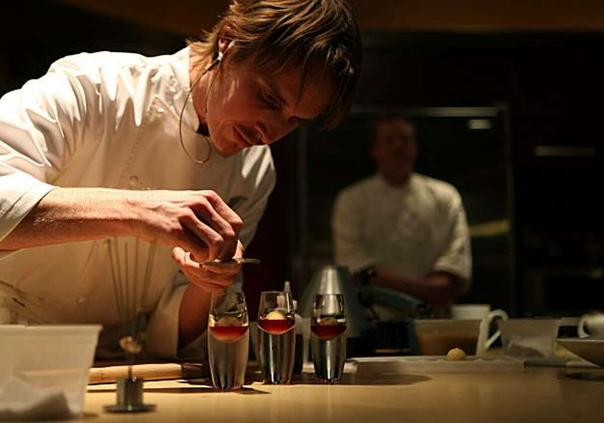 Nationally known celebrity chef Grant Achatz, adds the finishing touch to his frozen yogurt balls inside coconut butter, with pomegranate juice, during a demonstration, before signing copies of his cookbook, at Now We're Cookin in Evanston, Wednesday April 1, 2009.