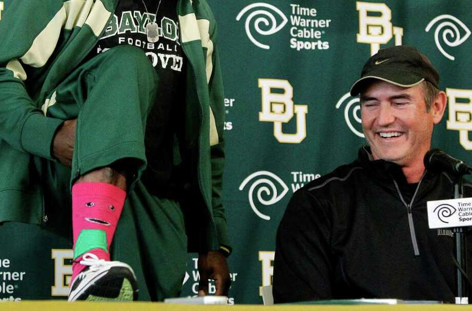 Baylor coach Art Briles, right, laughs as Heisman Trophy winner Robert Griffin III shows off his Barney character socks during a news conference where Griffin announced that he will skip his senior season to enter the NFL draft, Wednesday, Jan. 11, 2012, in Waco, Texas. (AP Photo/Tony Gutierrez) Photo: Tony Gutierrez, Associated Press / AP