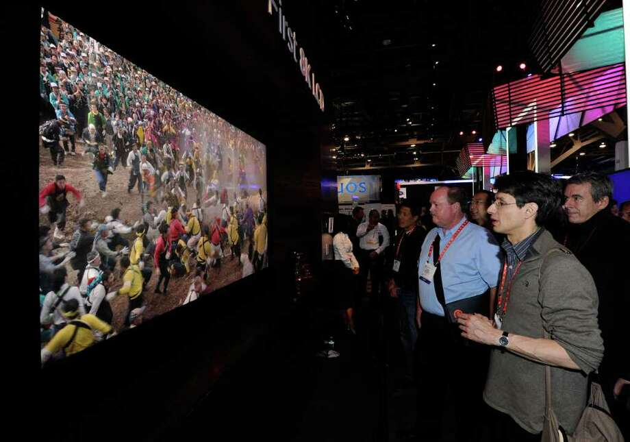 LAS VEGAS, NV - JANUARY 10:  Attendees look at what Sharp Electronics calls the world's first 8K resolution display technology on an 85-inch LED display prototype at the Sharp booth at the 2012 International Consumer Electronics Show at the Las Vegas Convention Center January 10, 2012 in Las Vegas, Nevada. The 8K technology is 7680 x 4230, 16 times greater than 1080p resolution and utilizes 33 million pixels on the 85-inch LED TV. CES, the world's largest annual consumer technology trade show, runs through January 13 and is expected to feature 2,700 exhibitors showing off their latest products and services to about 140,000 attendees. Photo: Ethan Miller, Getty Images / 2012 Getty Images