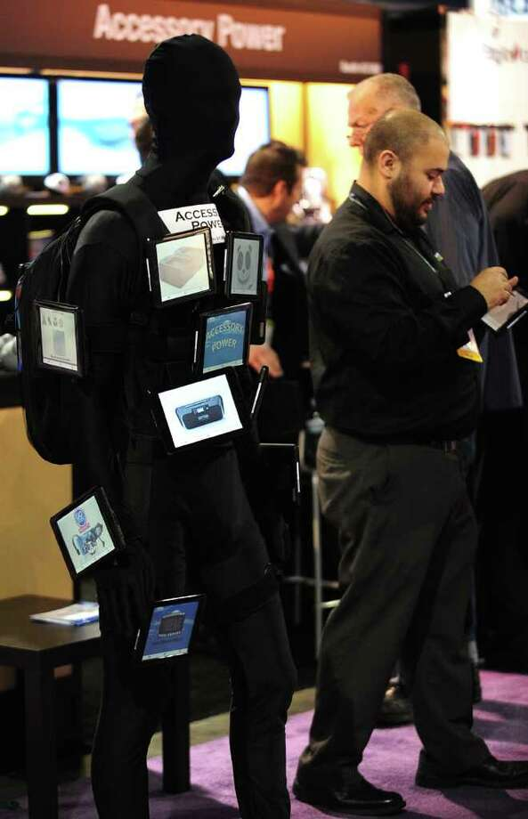 A man walks past Accesory Power Tablet Man (L) roaming the hall between booths at the International Consumer Electronics Show (CES) in Las Vegas, Nevada, on January 11, 2012.  The host of CES, the Consumer Electronics Association, has forecast worldwide spending on consumer electronics to surpass $1 trillion this year for the first time with smartphones and tablet computers leading the way. AFP PHOTO / Frederic J. BROWN Photo: FREDERIC J. BROWN, AFP/Getty Images / 2012 AFP