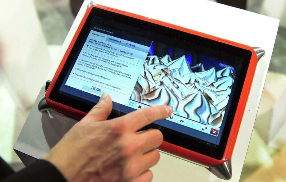 Guillame Hepp of Qooq-Unowhy gives a demonstration of the Qooq Cooking Tablet, a water-resistant sturdy device designed for use in the kitchen that runs off a Linux-based operating system with a kitchen-centric emphasis on recipes and food preparation, at the International Consumer Electronics Show (CES) in Las Vegas, Nevada, on January 11, 2012.  The host of CES, the Consumer Electronics Association, has forecast worldwide spending on consumer electronics to surpass $1 trillion this year for the first time with smartphones and tablet computers leading the way. AFP PHOTO / Frederic J. BROWN Photo: FREDERIC J. BROWN, AFP/Getty Images / 2012 AFP