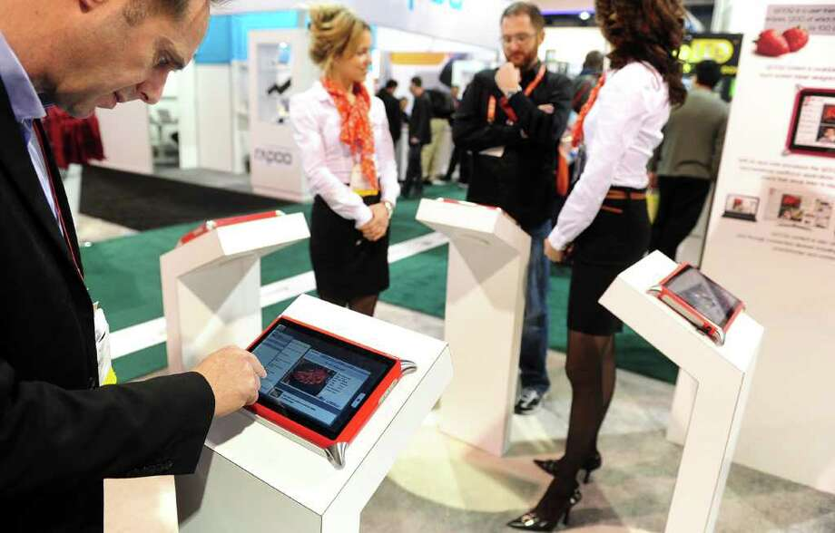 Guillame Hepp of Qooq-Unowhy (L) gives a demonstration of the Qooq Cooking Tablet, a water-resistant sturdy device designed for use in the kitchen that runs off a Linux-based operating system with a kitchen-centric emphasis on recipes and food preparation, at the International Consumer Electronics Show (CES) in Las Vegas, Nevada, on January 11, 2012.  The host of CES, the Consumer Electronics Association, has forecast worldwide spending on consumer electronics to surpass $1 trillion this year for the first time with smartphones and tablet computers leading the way. AFP PHOTO / Frederic J. BROWN Photo: FREDERIC J. BROWN, AFP/Getty Images / 2012 AFP