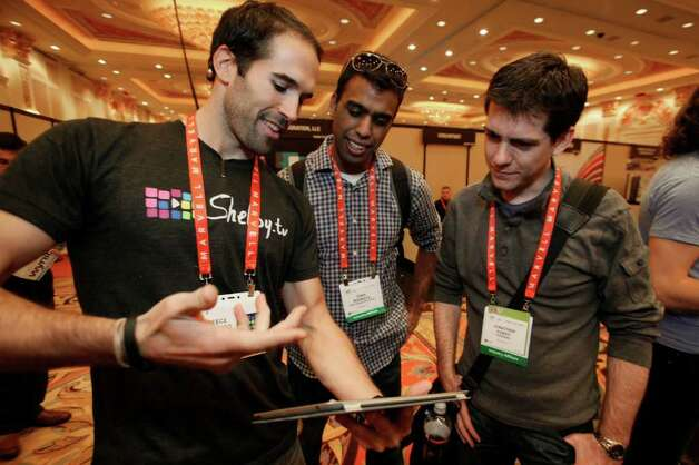 Several attendees get a closer look at a gadget at Eureka Park, the premier destination at the 2012 International CES in Las Vegas. Photo: COURTESY PHOTO