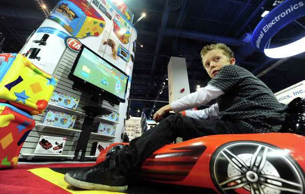 A child looks back while playing a game from an inflatable sports car at the display booth of CTA, which offers gaming accesories, at the International Consumer Electronics Show (CES) in Las Vegas, Nevada, on January 11, 2012. The host of CES, the Consumer Electronics Association, has forecast worldwide spending on consumer electronics to surpass $1 trillion this year for the first time with smartphones and tablet computers leading the way. AFP PHOTO / Frederic J. BROWN Photo: FREDERIC J. BROWN, AFP/Getty Images / 2012 AFP