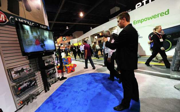 Jakub Ginda of CTA, which offers gaming accesories,  uses the US Army Elite Force Assault Rifle Controller for Playstation 3 and Playstation Move, at the International Consumer Electronics Show (CES) in Las Vegas, Nevada, on January 11, 2012. The host of CES, the Consumer Electronics Association, has forecast worldwide spending on consumer electronics to surpass $1 trillion this year for the first time with smartphones and tablet computers leading the way. AFP PHOTO / Frederic J. BROWN Photo: FREDERIC J. BROWN, AFP/Getty Images / 2012 AFP