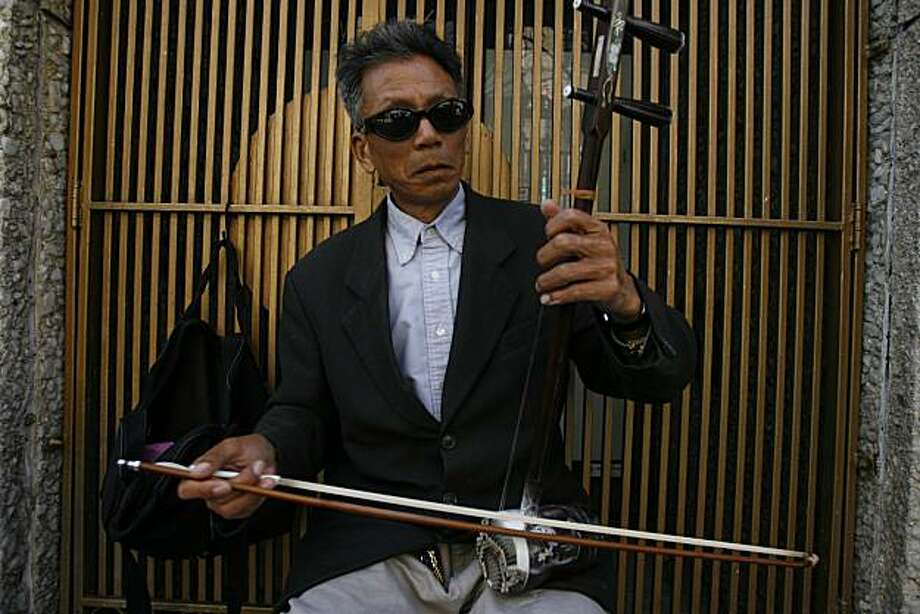Liu Zhong Qi playing the Erhu Fiddle along Grant St. Photo: Eric Luse, The Chronicle