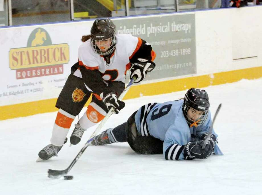 Ridgefield's Maggie McSpedon wins control of the puck from Wilton's Erin O'Connell during their game at the Ridgefield Winter Garden on Wednesday, Jan. 11, 2011. Ridgefield beat Wilton 4-2. Photo: Jason Rearick / The News-Times