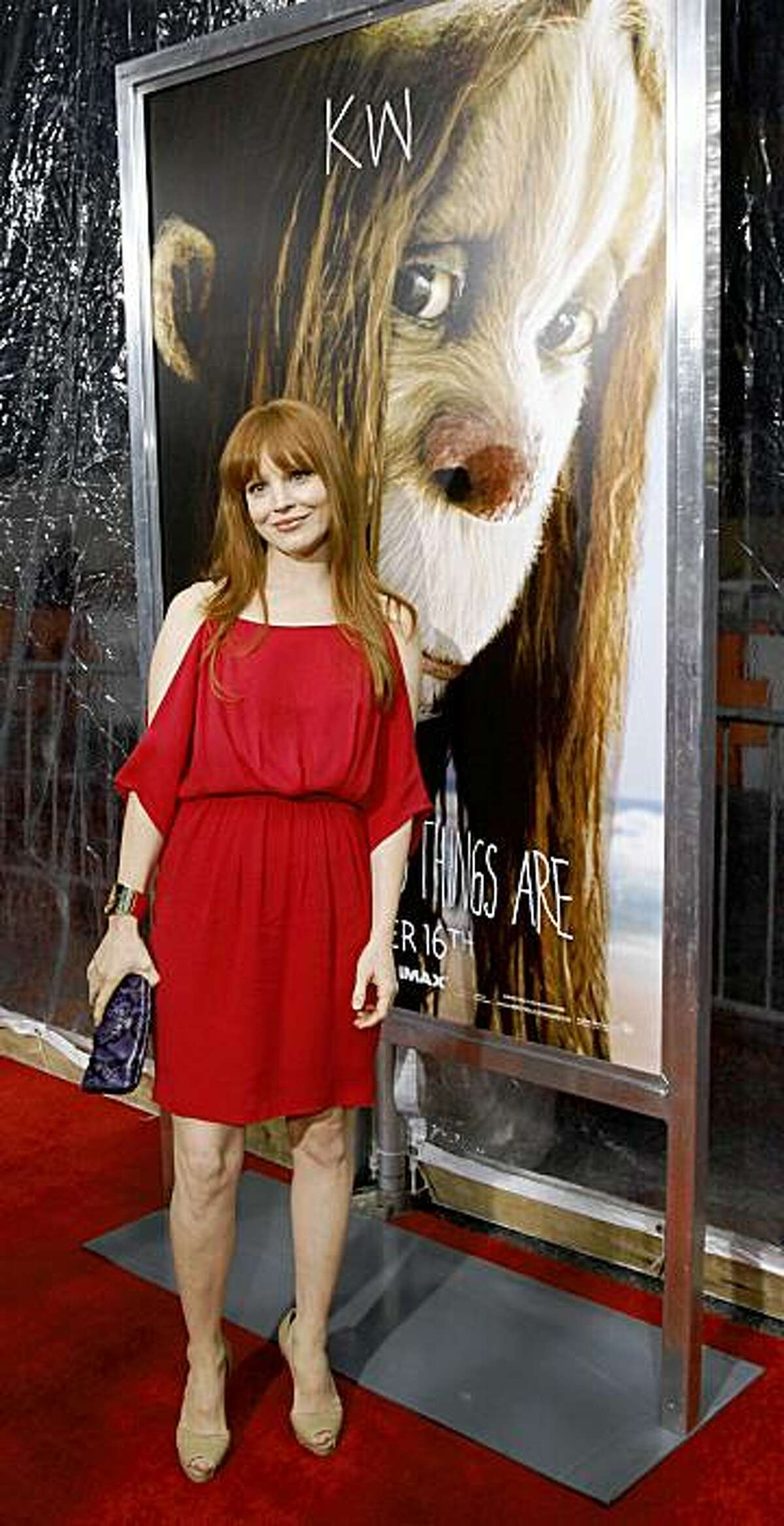 Lauren Ambrose stands in front of a poster of the character 'KW', who she plays in the film