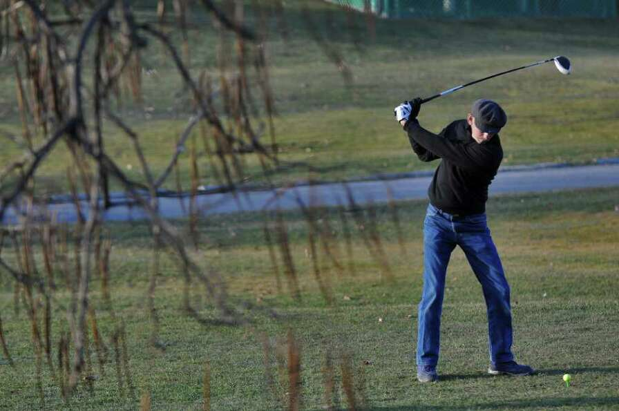 Dick O'Donnell of Troy takes advantage of warm weather to practice at the driving range of the Frear