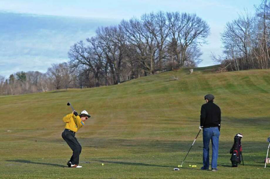 "Johnny Wattendorf, left, and Dick O'Donnell, right, both of Troy take advantage of warm weather to practice at the driving range of the Frear Park Municipal Golf Course on Wednesday Jan. 11, 2012 in Troy, NY.  Wattendorf said that ""Today is a gift,'""while speaking of the unseasonably warm weather, in the high 30's to low 40's.  (Philip Kamrass / Times Union ) Photo: Philip Kamrass / 10016072A"