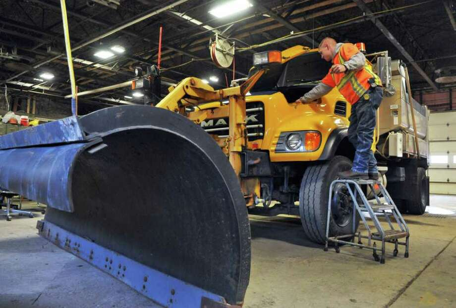 Plow operator Kevin Stewart readies a snow plow for what-ever tomorrow's weather might be at the Latham NYS DOT shop Wednesday Jan. 11, 2012.   (John Carl D'Annibale / Times Union) Photo: John Carl D'Annibale