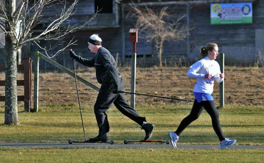 A rollerskier and jogger share the path and good weather at The Crossings in Colonie Wednesday Jan. 11, 2012.   (John Carl D'Annibale / Times Union) Photo: John Carl D'Annibale