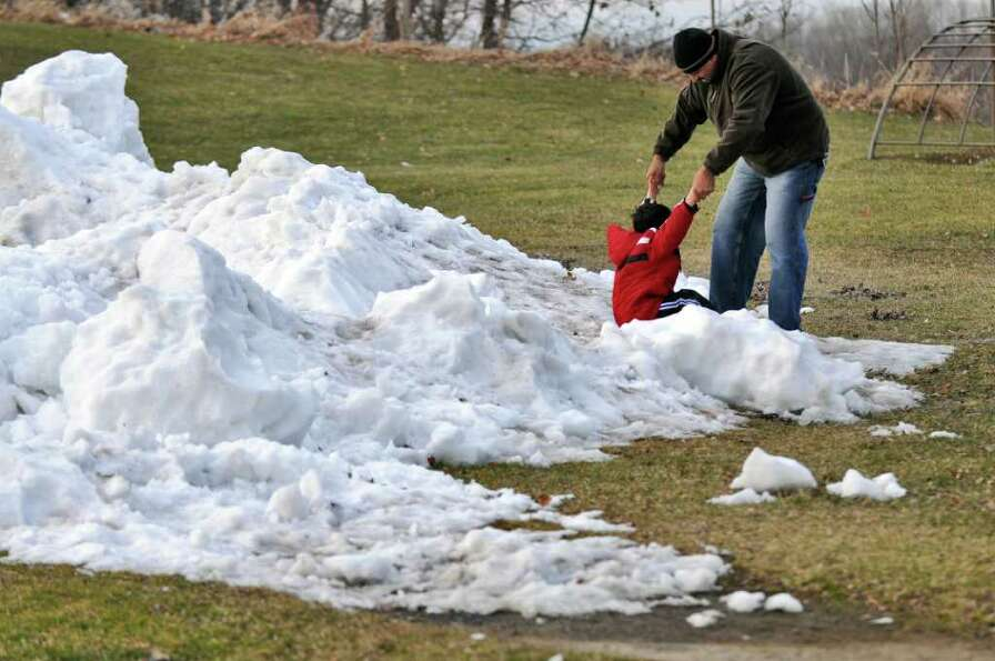 Raja Abbas of Troy and his son Sami, 4, play in snow and ice taken from the ice hockey rink at Frear