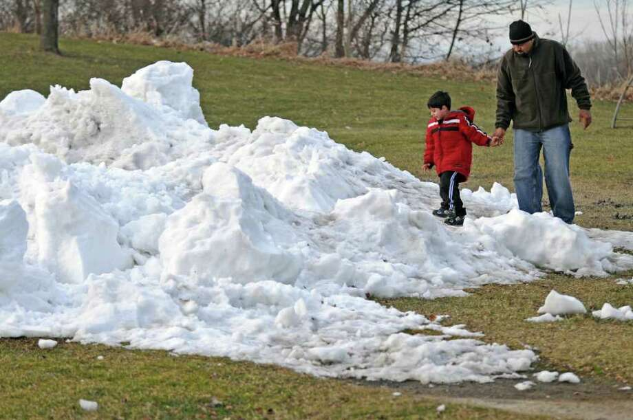 Raja Abbas of Troy and his son Sami, 4, play in snow and ice taken from the ice hockey rink at Frear Park on Wednesday Jan. 11, 2012 in Troy, NY.  Raja said that his son saw the snow on the previous day while driving by, and asked his dad to stop. (Philip Kamrass / Times Union ) Photo: Philip Kamrass / 10016072A