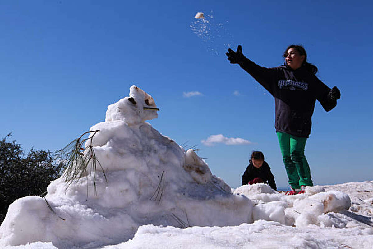 Stephanie Magallon, 10, right, and little sister, Jacqueline Magallon, 3, throw snow balls at their brother Juan Magallon, 13, (NOT PICTURED) after building a snowman at Juniper Camp Ground overlook in Mt. Diablo State Park in Clayton, Calif. on Tuesday, February 22, 2011. Kat Wade / Special to the Chronicle