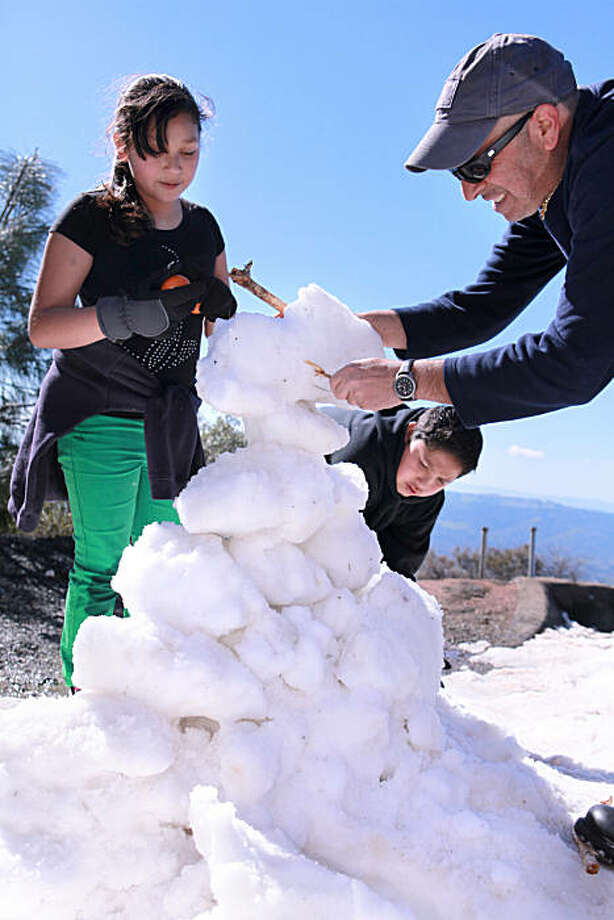 From Left,  Stephanie Magallon, 10 ,  and Juan Magallon, 13, of Concord, get help building a snowman from Thanasis Golematis, of Pittsburg at Juniper Camp Ground overlook in Mt. Diablo State Park in Clayton, Calif. on Tuesday, February 22, 2011.    Kat Wade / Special to the Chronicle Photo: Kat Wade, Special To The Chronicle