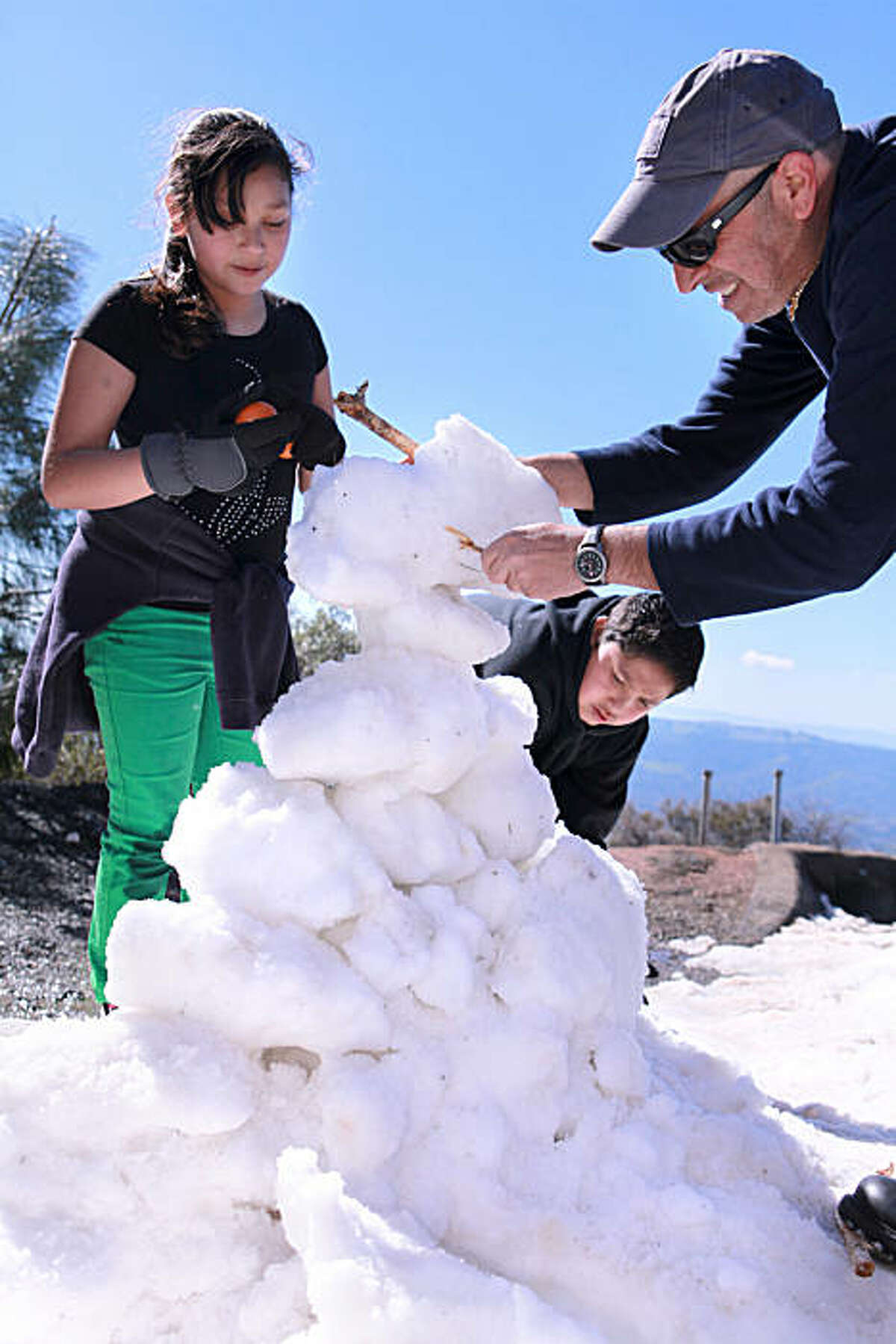 From Left, Stephanie Magallon, 10 , and Juan Magallon, 13, of Concord, get help building a snowman from Thanasis Golematis, of Pittsburg at Juniper Camp Ground overlook in Mt. Diablo State Park in Clayton, Calif. on Tuesday, February 22, 2011. Kat Wade / Special to the Chronicle