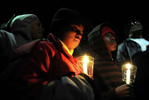 Ten-year-olds Gregory Thompson, left, and Canon Aarons hold candles Wednesday, Jan. 11. 2012 during an anti-violence rally on the steps of City Hall Annex in Bridgeport, Conn.  Hundreds of residents marched from the East End Police Substation on Stratford Avenue to City Hall in response to the shooting of 14-year-old Justin Thompson. Photo: Autumn Driscoll / Connecticut Post