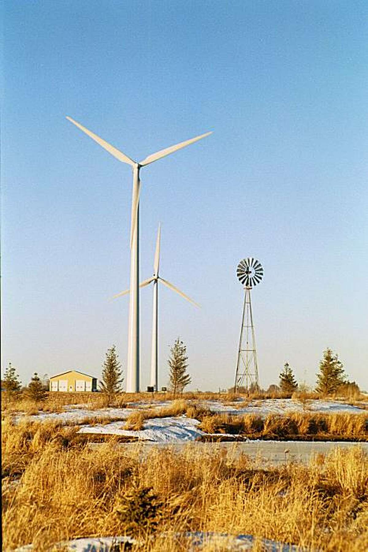 A community wind farm in Minnesota has two large wind turbines sited on agricultural land and an older windmill.