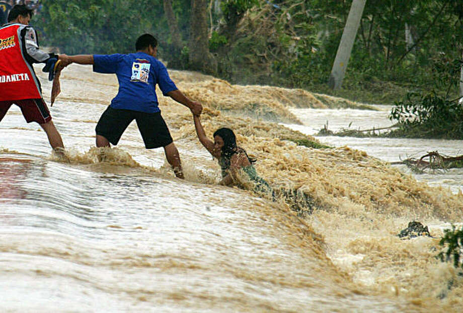 A woman holds on to a man as strong currents pull her away from the streets in Rosales town, northern Philippines, on Friday, Oct. 9, 2009. Hundreds of people have been killed in the country's worst flooding in 40 years after back-to-back storms started pounding the country's north Sept. 26. Photo: Mike Alquinto, AP