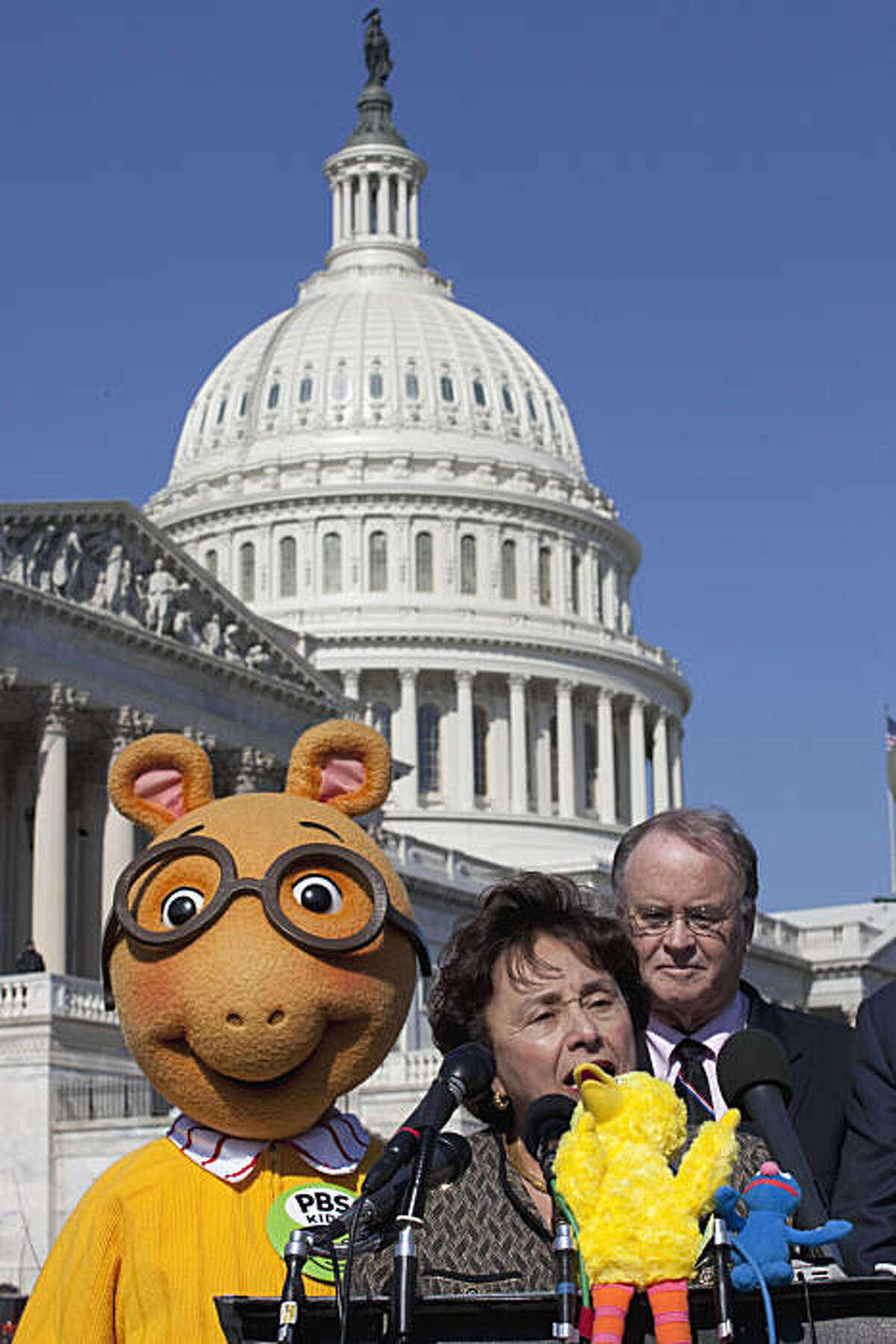 Arthur the Aardvark and Rep. Sam Farr, D-Calif., listen as Rep. Nita Lowey, D. N.Y., speaks during a news conference on Capitol Hill in Washington, Wednesday, Feb. 16, 2011, to discuss the future of Public Broadcasting.