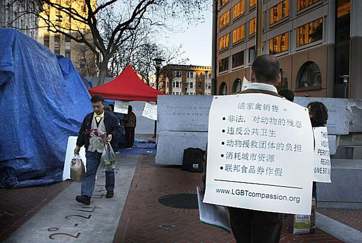 A customer walks by with a bagged chicken as activist Andrew Zollman protests wearing a sign near the truck (with blue tarp housing chickens) of Raymond Young Poultry at the U.N. Plaza Heart of the City Farmers Market in San Francisco Calif., on Wednesday, February 2, 2011.