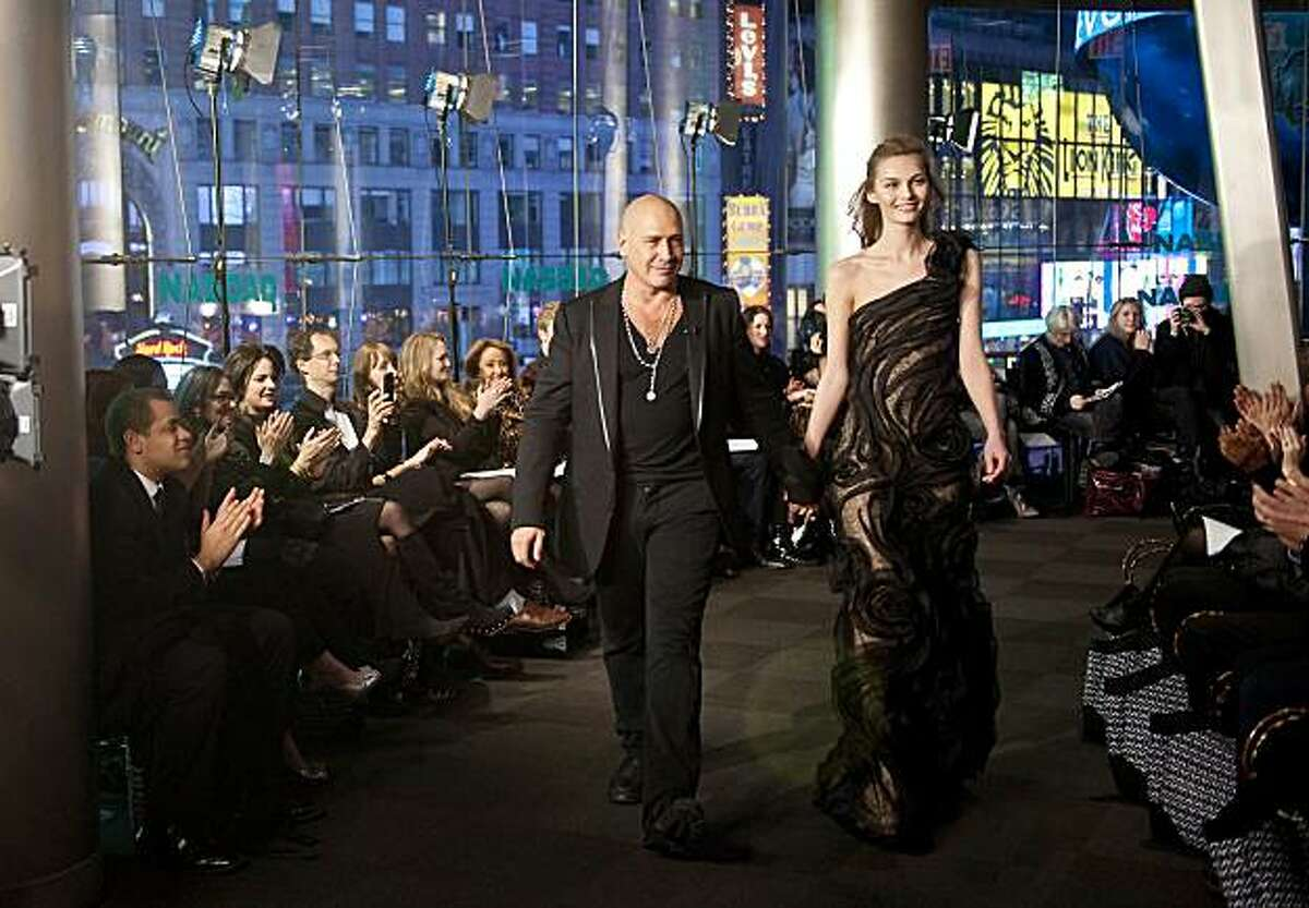 Designer Carmen Marc Valvo, escorted by a model, walks the runway after his Fall fashion show at the NASDAQ Market Site during Fashion Week Sunday, Feb. 13, 2011 in New York.
