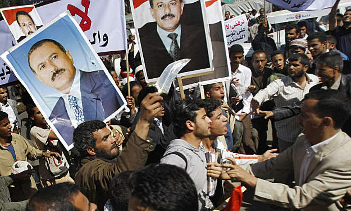 Yemeni anti-government protestors, right, scuffle with government supporters during a rally demanding political reform and the resignation of President Ali Abdullah Saleh in Sanaa, Yemen, Sunday, Feb. 13, 2011. Yemeni police have clashed with anti-government protesters demanding political reform and the resignation of President Ali Abdullah Saleh. Several thousand protesters, many of them university students, tried to reach the central square in the capital of Sanaa on Sunday, but were pushed back by police using clubs. It was the third straight day of anti-government protests.