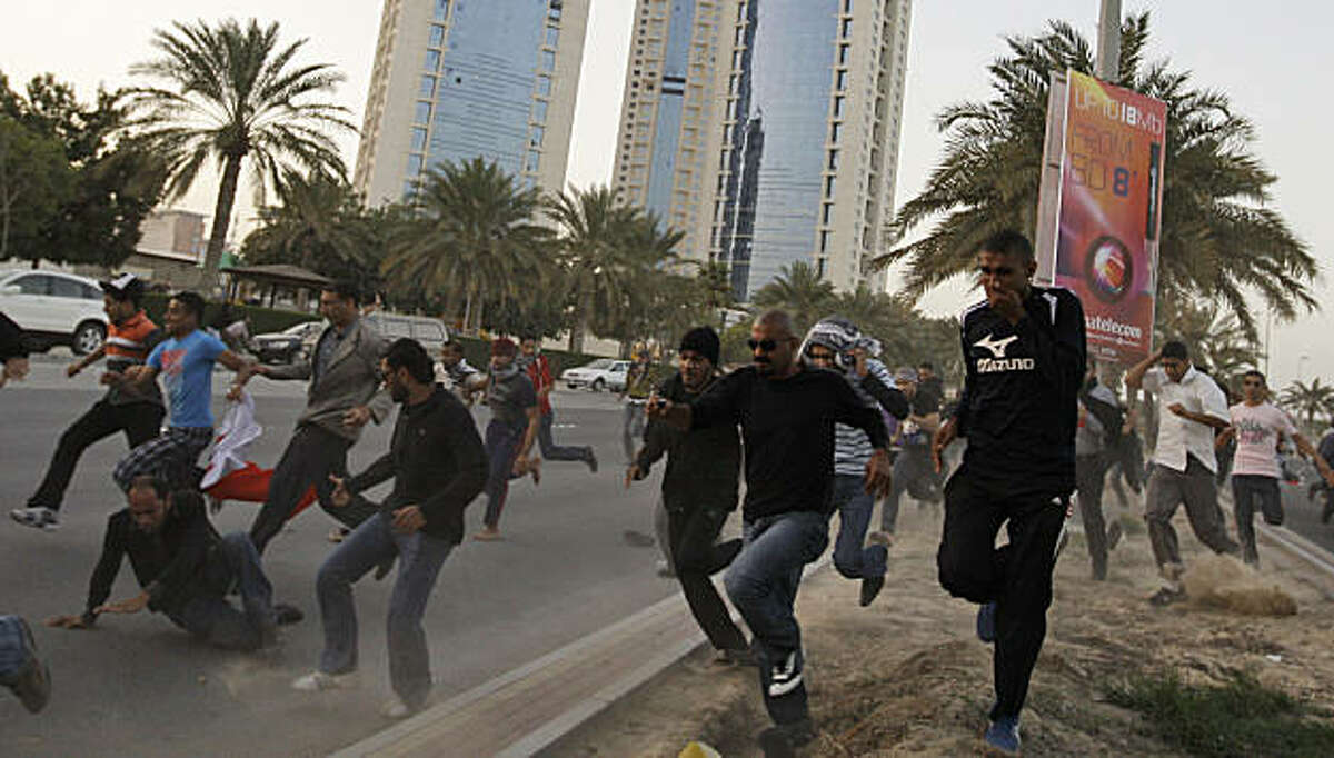 Bahraini anti-government demonstrators run during clashes between protesters and the Bahraini army during a demonstration in Manama, Bahrain, Friday, Feb. 18, 2011.