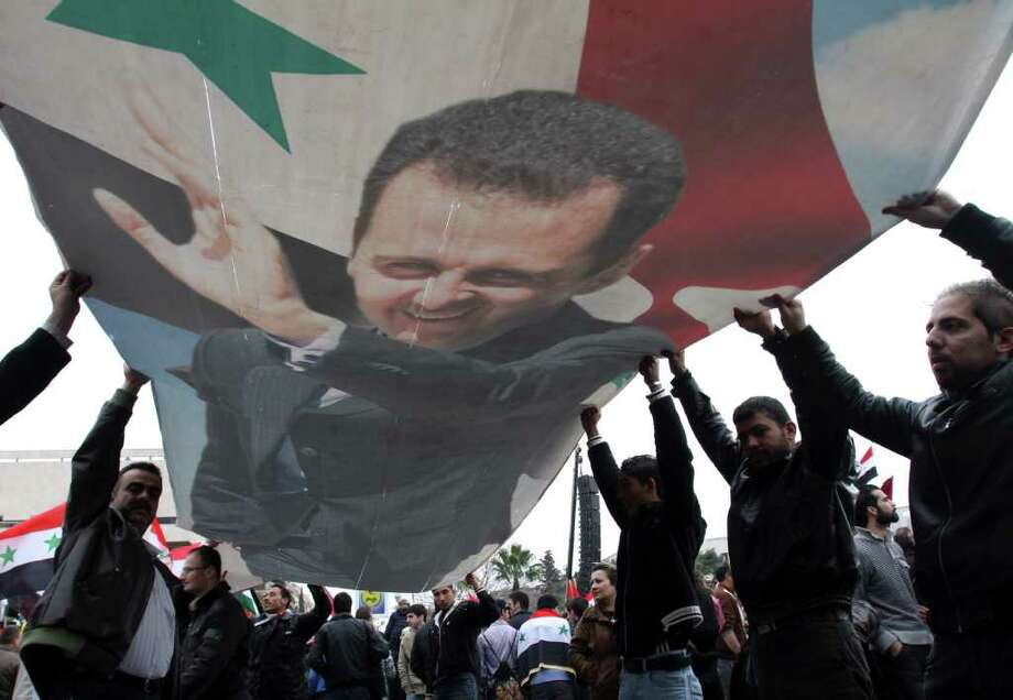 Supporters of Syrian President Bashar Assad rally Wednesday in Damascus. Meanwhile, a Western journalist was killed in the city of Homs. Photo: Bassem Tellawi / AP