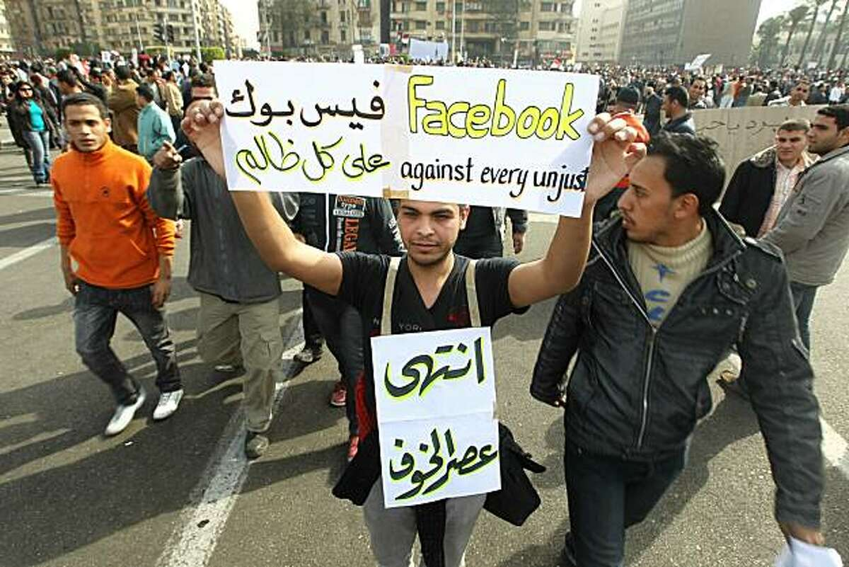 An Egyptian man hold up a sign praising the social network website Facebook, joins others in Cairo's Tahrir Square heeding a call by the opposition for a