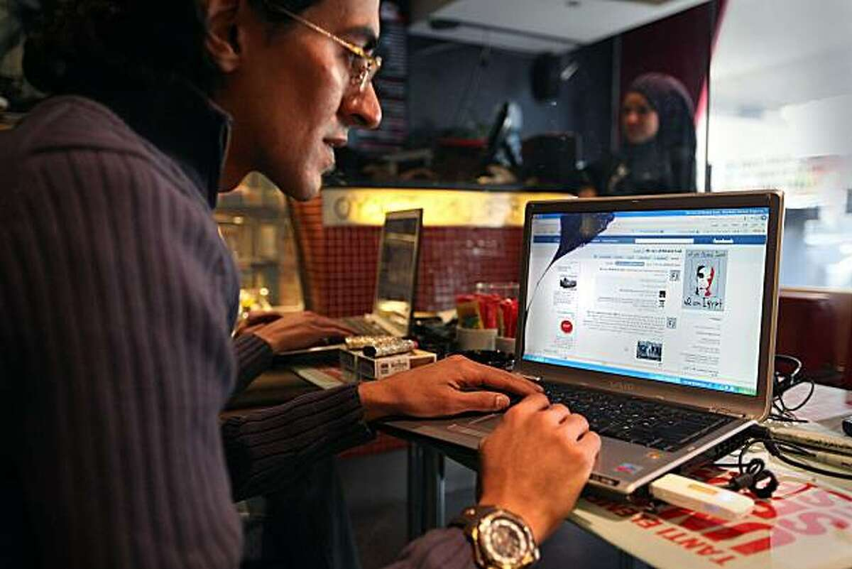 CAIRO, EGYPT - JANUARY 27: A man looks at a laptop computer displaying Facebook in a cafe on January 27, 2011 in Cairo, Egypt. Thousands of police are on the streets of the capital and hundreds of arrests have been made in an attempt to quell anti-government demonstrations.