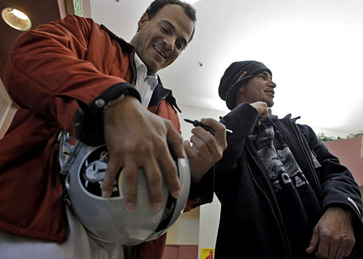 Former Oakland Raider Jarrod Cooper signs a helmet that he gave to Vince Faltis at a press conference honoring Faltis, Thursday Feb 17, 2011, at the Oakland Animal Shelter in Oakland, Calif. Faltis video taping Charles Black beating his dog, Blueberry, which lead to a conviction and sentenced Black to four years in prison.
