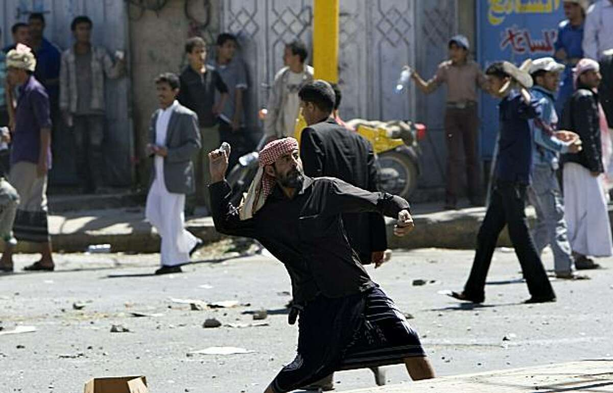 Yemeni anti-government protesters throw stones towards regime loyalists during clashes in central Sanaa on February 17, 2011. At least 12 people were injured and police fired warning shots during the fierce clashes, an AFP reporter said.