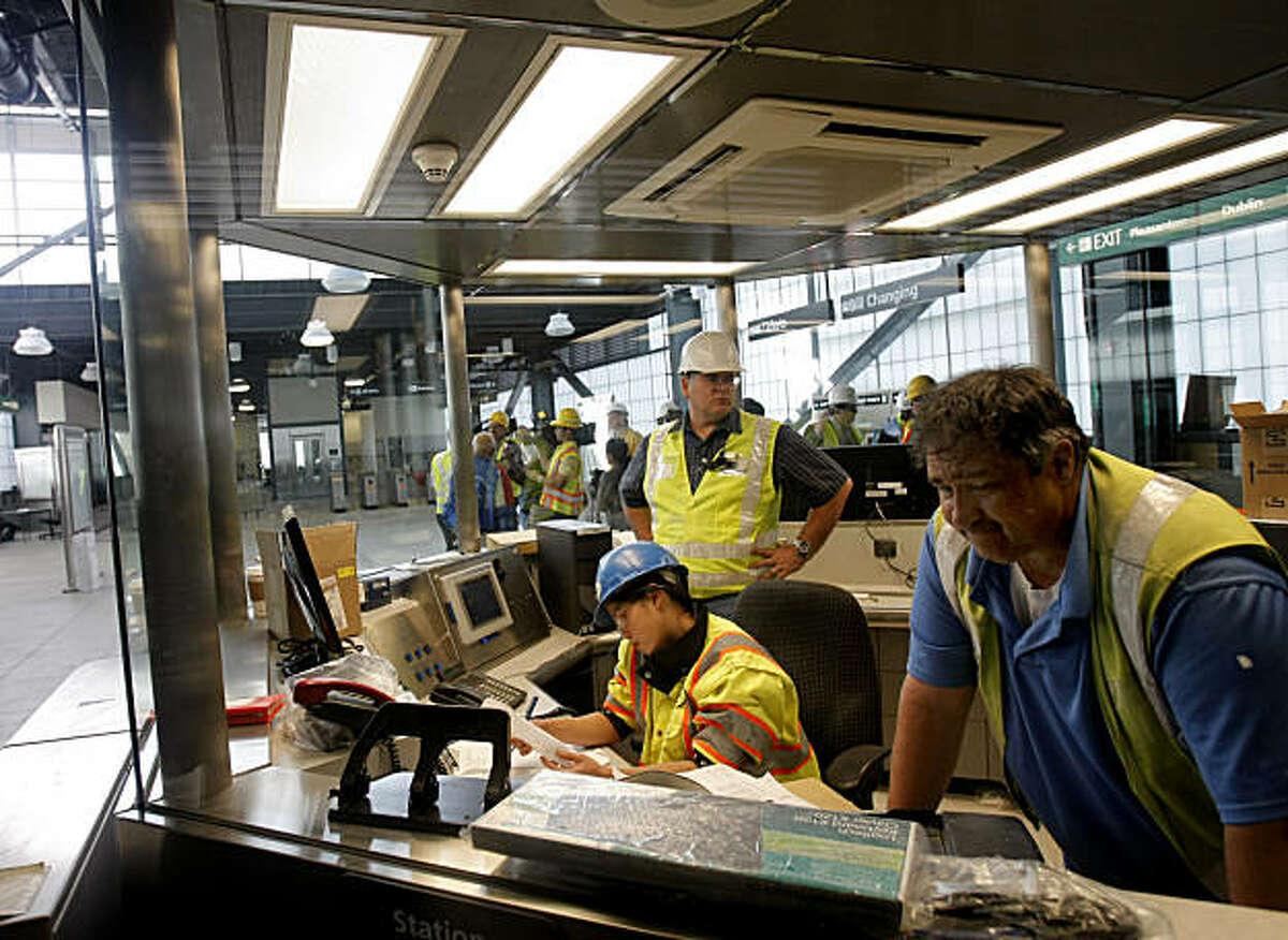 Rory Shortred (far right), Sylvia Hartanto (bottom center), and Carlyle Potts, work in a BART fare gate during a media tour through BART's new 44th station set to open Feb. 18 in Dublin, Calif., on Friday, February 11, 2011.