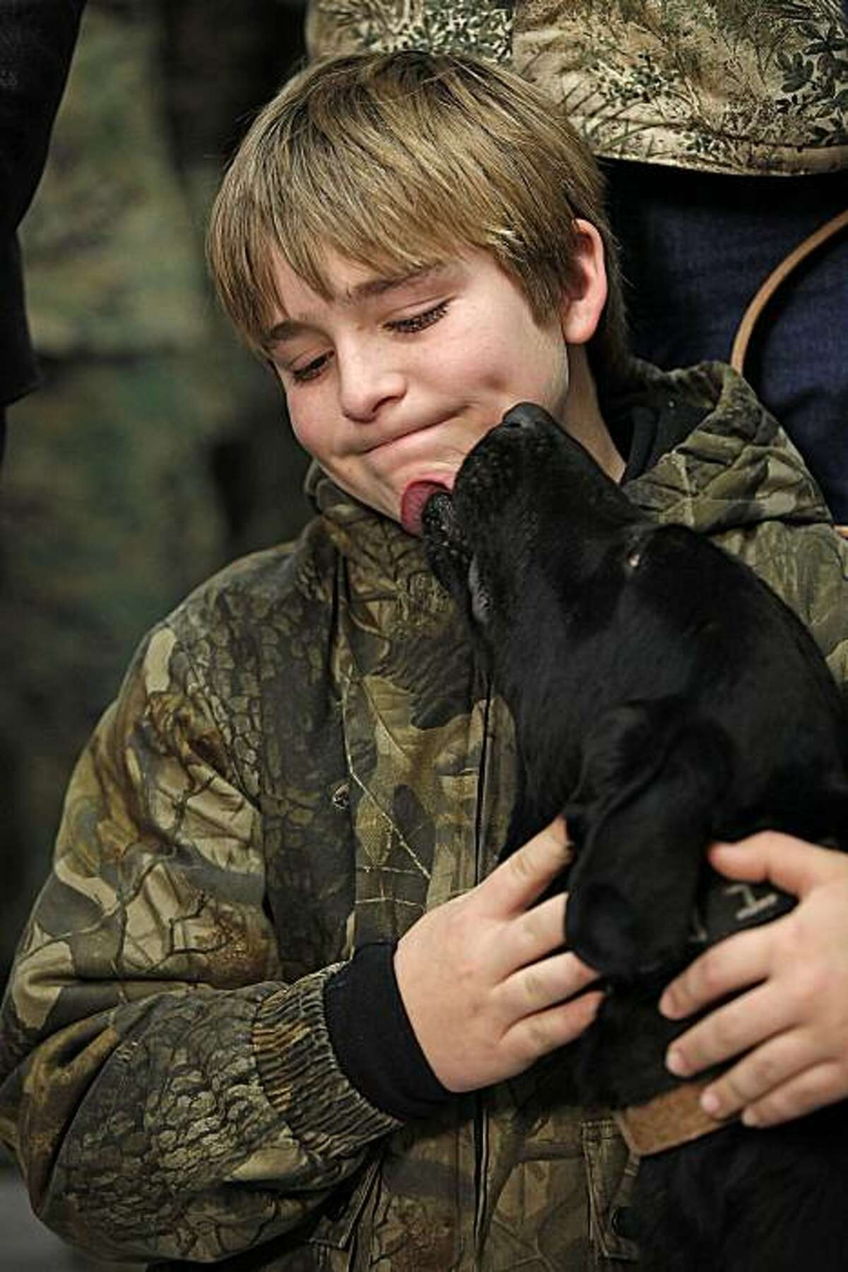 Bomb-sniffing Labrador, Eli, licks Brady Rusk, 12, during an adoption ceremony at Lackland Air Force Base in San Antonio, Thursday, Feb. 3, 2011. . Rusk brother, U.S. Marine Pfc. Colton W. Rusk, was Eli's handler. Eli, a bomb-sniffing Labrador whose handler was killed in combat has new owners _ the family of the fallen U.S. Marine who the dog loyally obeyed in Afghanistan. (AP Photo/San Antonio Express-News, Jerry Lara) RUMBO DE SAN ANTONIO OUT; NO SALES; MAGS OUT