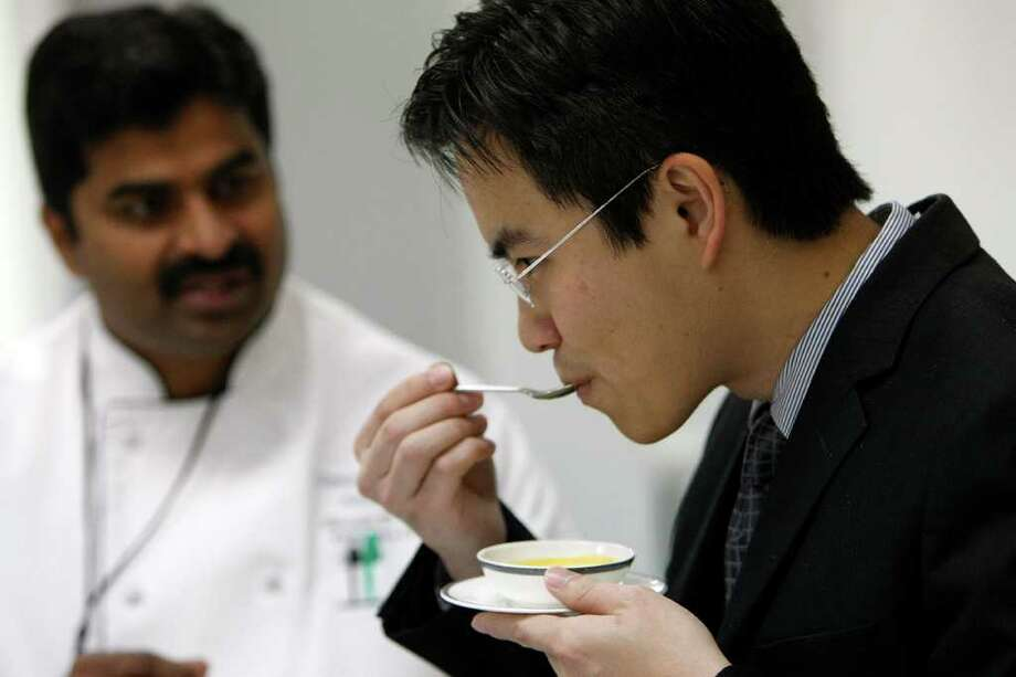 Executive chef Shashi Sanamvenkata with United looks on as Ronald Kwee with Singapore Airlines samples a roasted butternut squash soup as Sanamvenkata presented new food options for the Singapore Airlines flights from Houston to Moscow at Chelsea Food Services at Bush Intercontinental Airport Wednesday, Jan. 11, 2012, in Houston. Photo: Johnny Hanson, Houston Chronicle / © 2012  Houston Chronicle