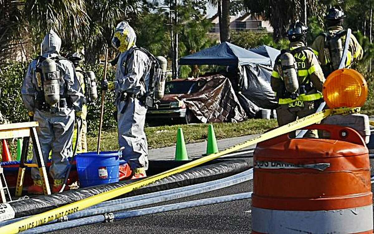 In this Feb. 15, 2011 photo, Palm Beach County firefighters in protective suits work near Jorge Barahona's pesticide truck, background, where it was found the night before along the side of Interstate 95 near West Palm Beach, Fla. The badly deteriorated body of Barahona's 10-year-old daughter was discovered in the truck hours after her critically injured twin brother was found having seizures in the front seat after being doused in acid by his father, according to officials. Barahona was lying on the ground near the truck with severe burns, apparently from gasoline he poured on himself. (AP Photo/Palm Beach Post, Richard Graulich) MAGS OUT; TV OUT; NO SALES