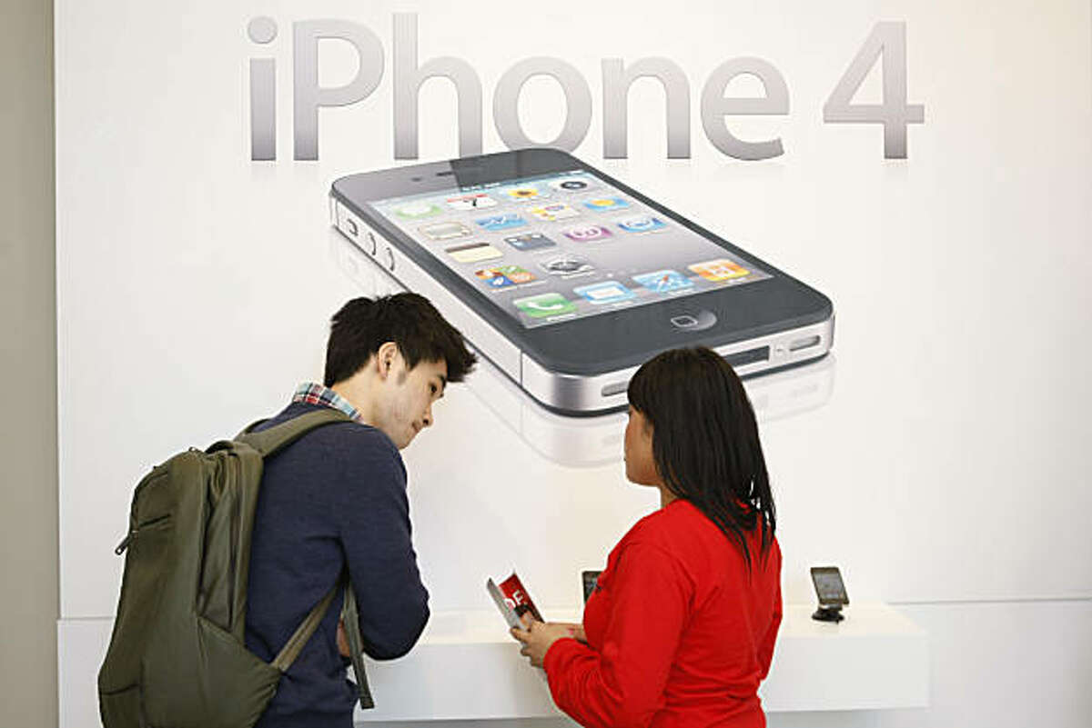 Hanmaro Kim (left) receives help purchasing an iPhone 4 at the Verizon Wireless store on Market Street in San Francisco Calif. on Thursday, Feb. 10, 2011.