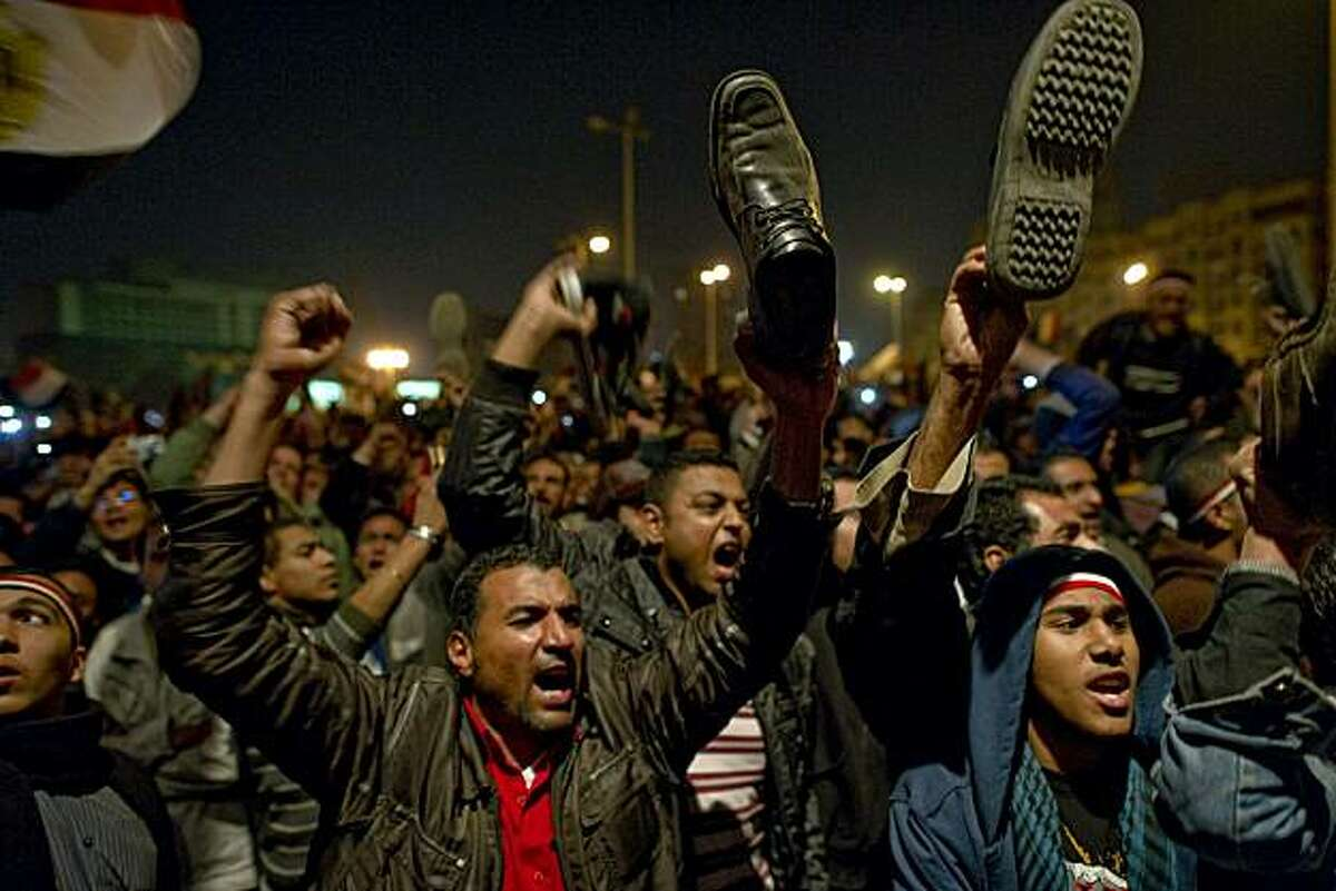 Egyptian anti-government demonstrators wave their shoes as they show their anger during a speech by Egyptian President Hosni Mubarak, who failed to announce his immediate resignation, as tens of thousands gathered in Cairo's Tahrir Square on February 10,2011. Embattled Mubarak delegated power on February 10, 2011 to his deputy and former intelligence chief Omar Suleiman and proposed constitutional reforms but said the transition to end his 30-year-reign would last until September.