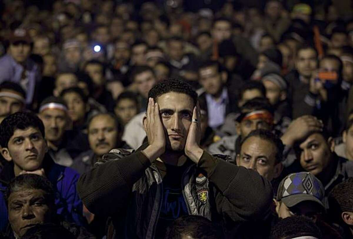 Anti-government protesters watch on big screen as Egyptian President Hosni Mubarak makes a televised statement to his nation in Tahrir Square in downtown Cairo, Egypt Thursday, Feb. 10, 2011. Egyptian President Hosni Mubarak announced he is handing his powers over to his vice president, Omar Suleiman, and ordered constitutional amendments Thursday. But the move means he retains his title of president and ensures regime control over the reform process, falling short of protester demands. Protesters in Cairo's central Tahrir Square, hoping he would announce his resignation outright, reacted in fury and disbelief.