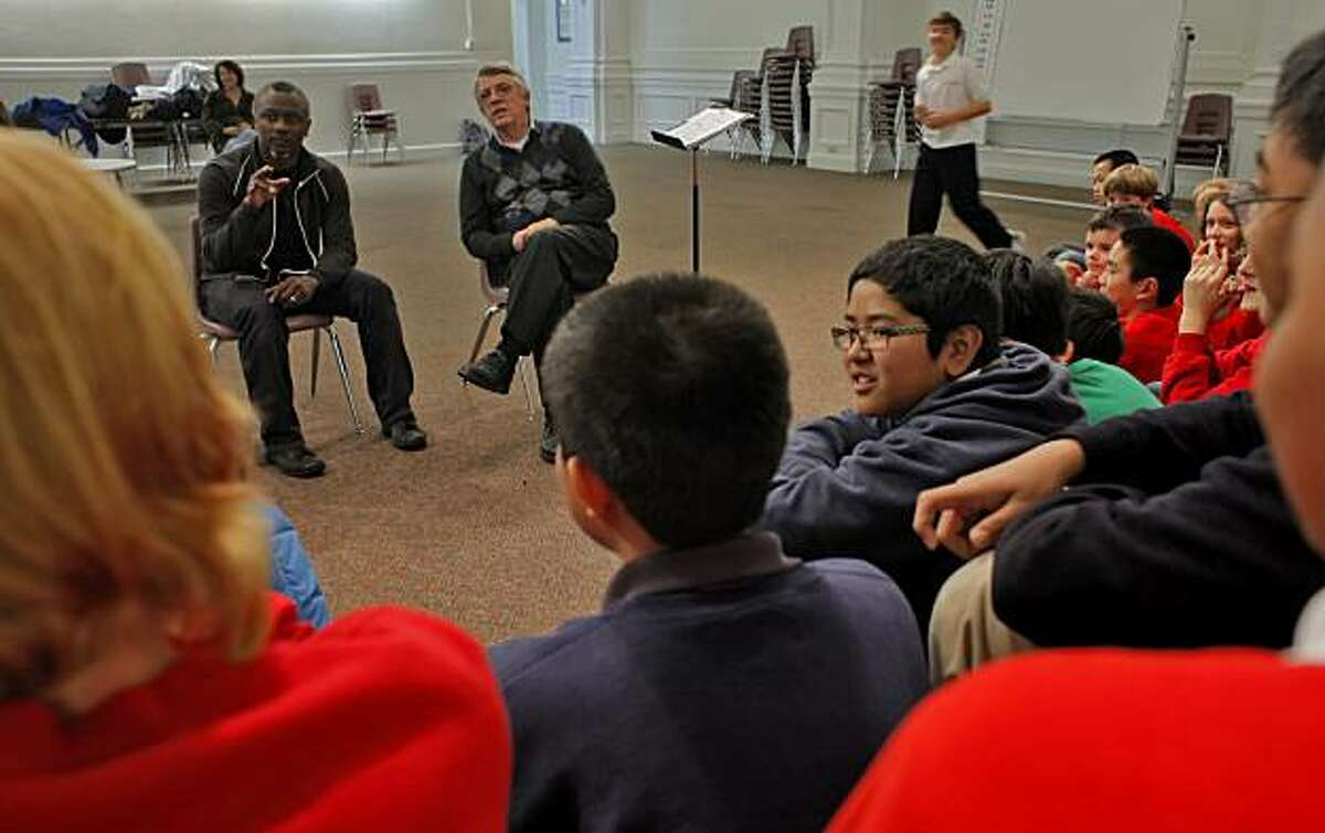 Choreographer Robert Moses, left, and conductor Ian Robertson question the boys of the San Francisco Boys Choir about their activities, during rehearsal, Wednesday January 19, 2011, in San Francisco, Calif. Robertson and choreographer Robert Moses are collaborating on a performance in the future.